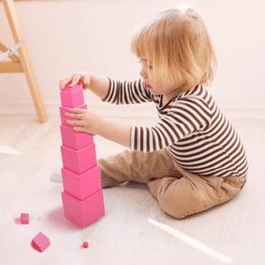 Enfant qui construit une tour rose montessori